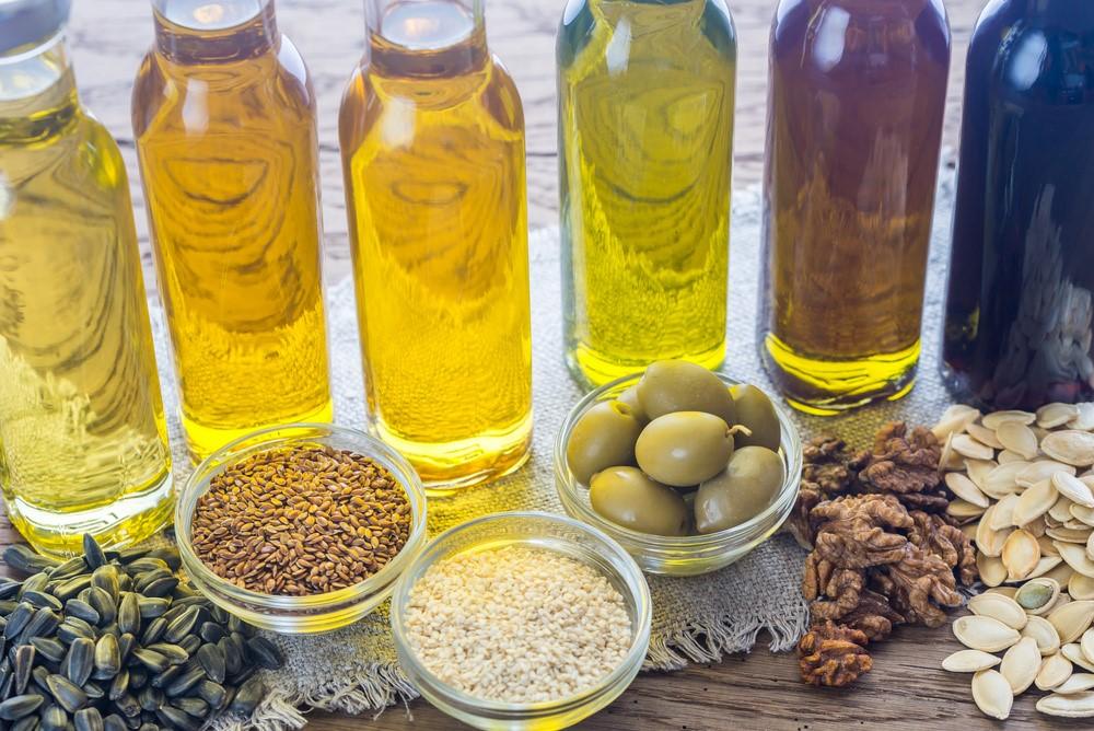 様々な油の瓶とオリーブ等の原料