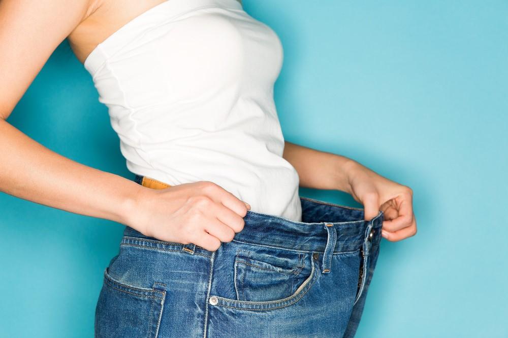 ダイエットに成功し、ズボンのサイズが合わなくなった女性