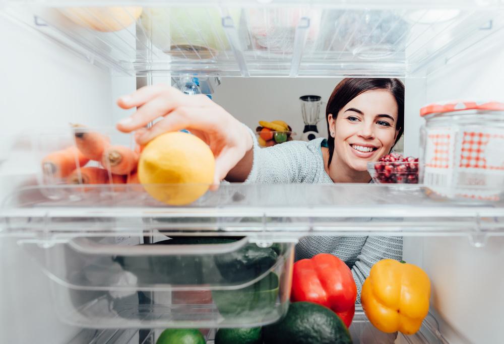 冷蔵庫の中からレモンを出そうとしている女性
