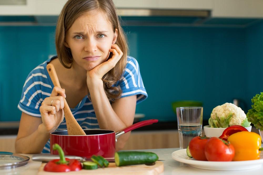 困った顔で鍋をかき混ぜている女性