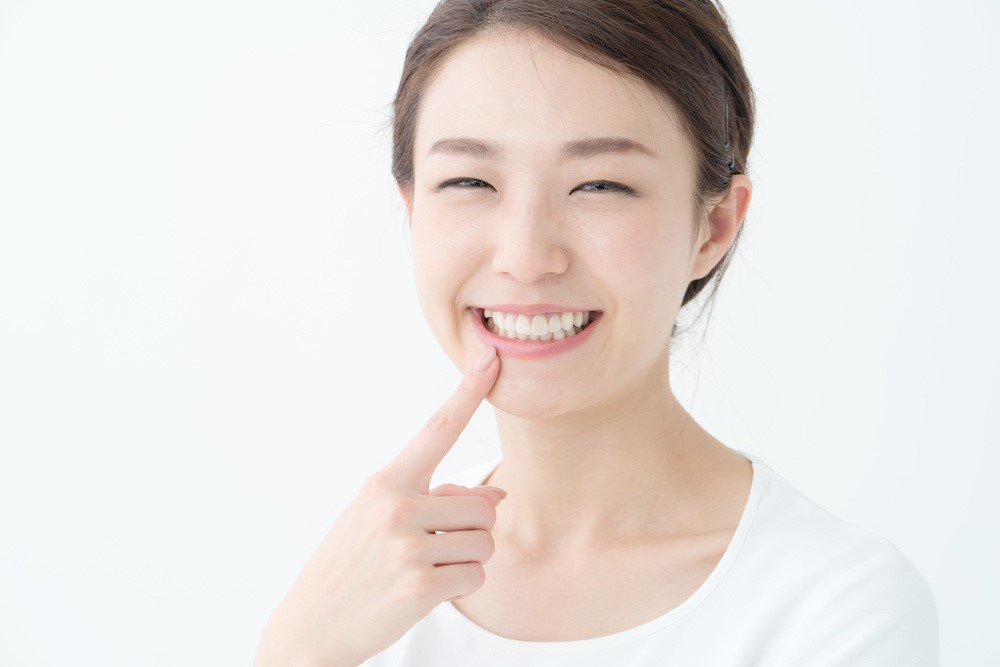 笑顔で歯を指さしている女性