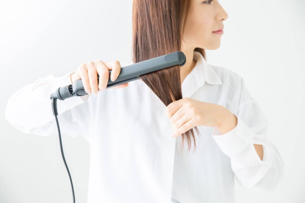 ヘアアイロンを髪にかけている女性