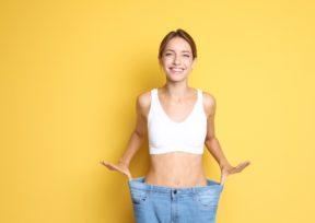 ダイエットに成功した女性が笑顔でウエストがゆるくなったジーンズをはいている