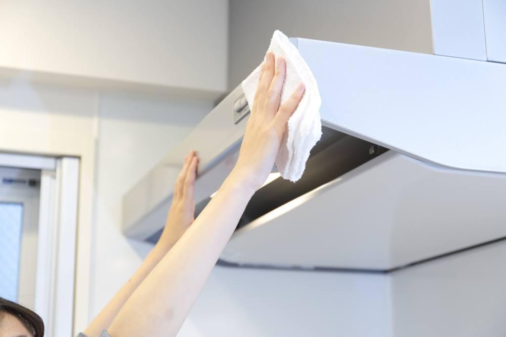 キッチンの換気扇を拭き掃除している
