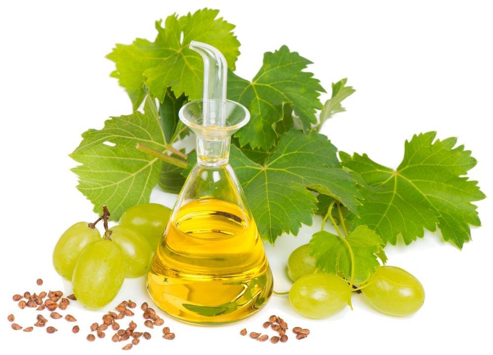 ブドウの実と種と容器に入ったグレープシードオイル