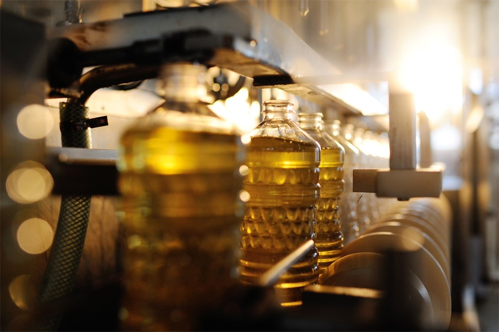 工場のレーンで容器に注がれるひまわり油