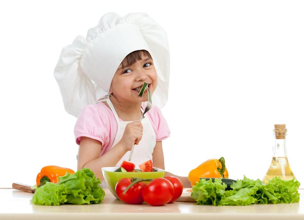 女の子がコック帽をかぶって野菜を食べている