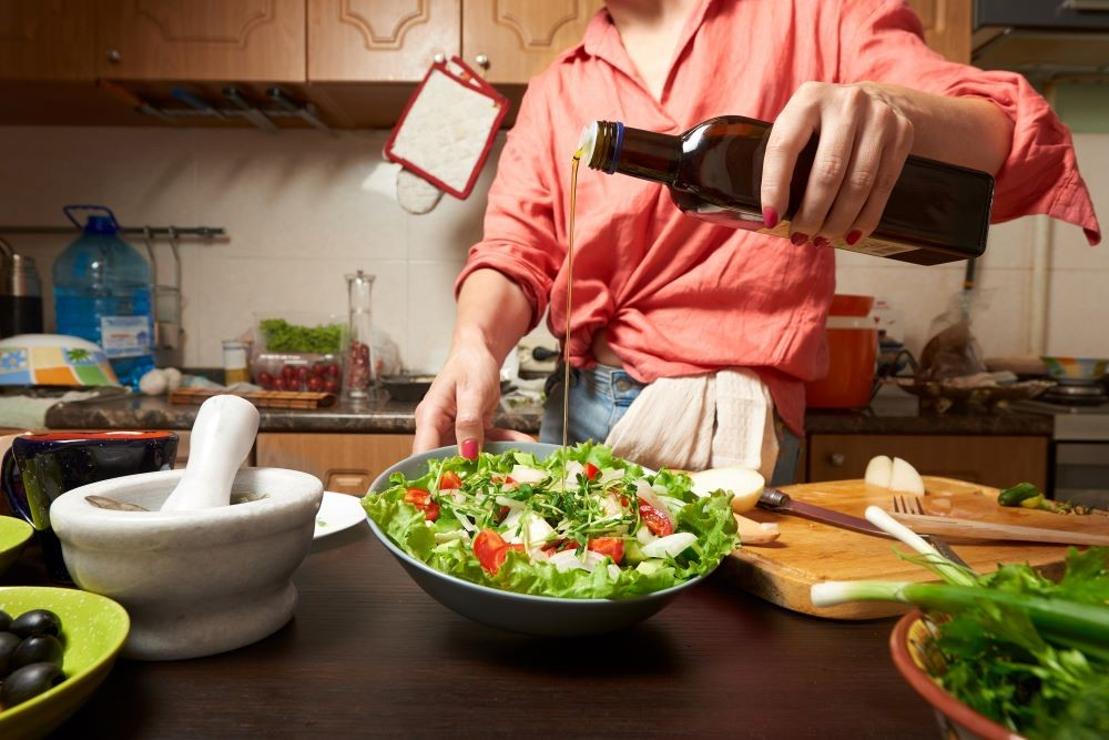 女性がサラダにグレープシードオイルをかけている