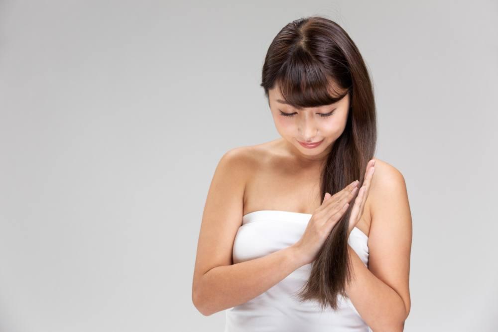 女性が髪の毛にココナッツオイルを塗っている