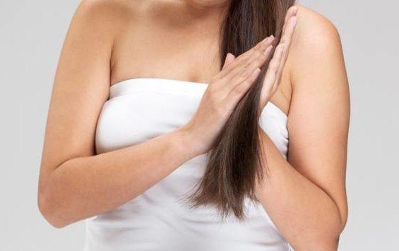 髪にココナッツオイルを塗っている女性