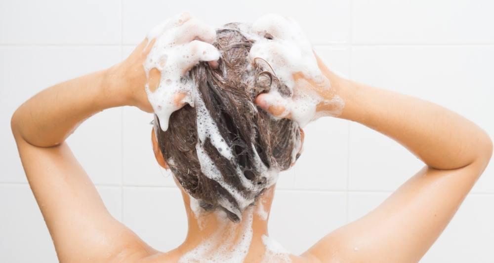 髪を泡立てて洗っている女性