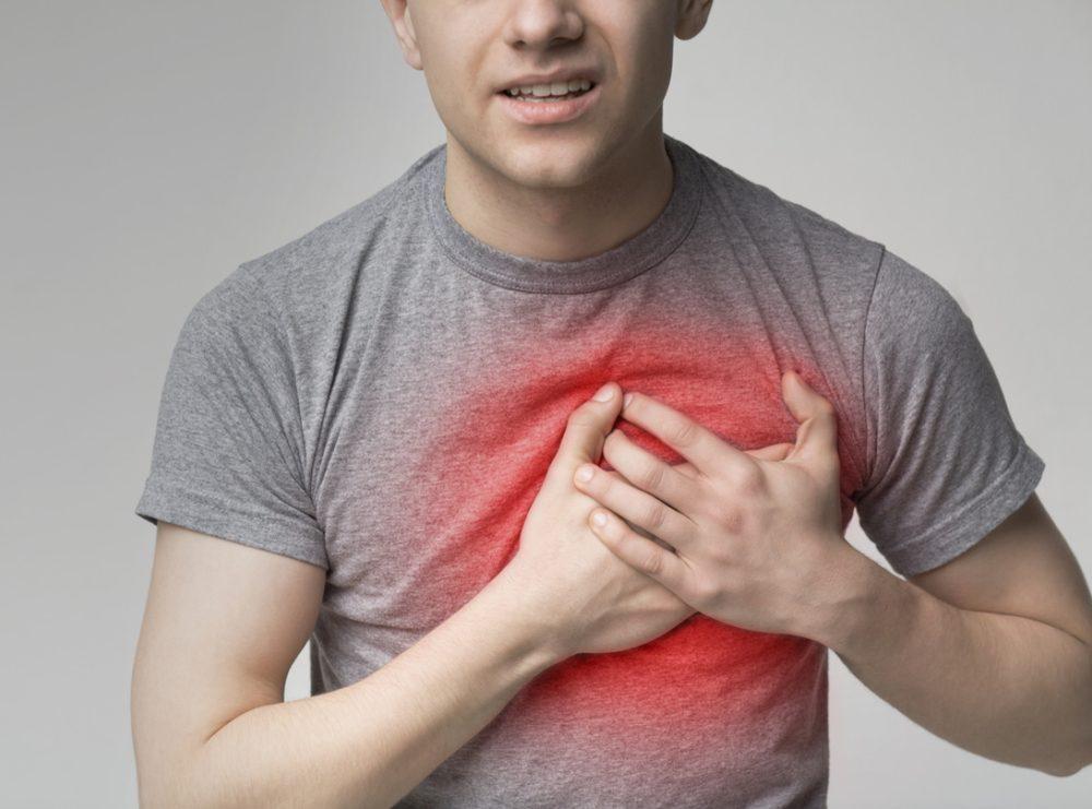 男性が心臓を苦しそうに抑えている