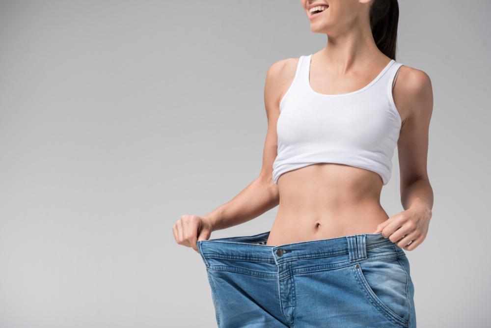 ダイエットに成功した女性が大きいサイズのジーンズを履いて笑っている