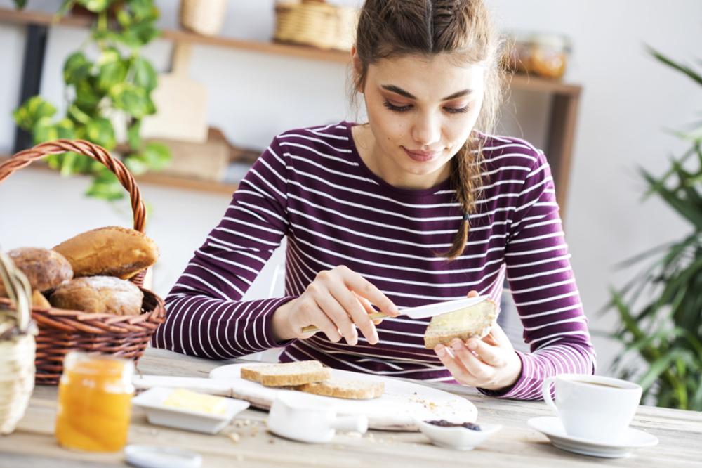 バターをパンに塗っている女性