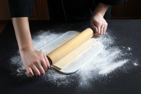 パイ生地を麺棒で伸ばしている