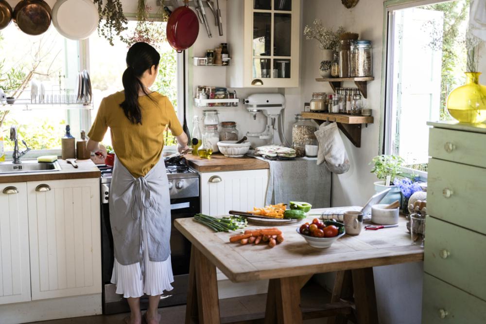 女性が台所に立ち、料理をしている