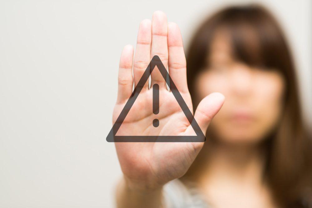 女性が危険を表すマークが書かれた手のひらを前に出している