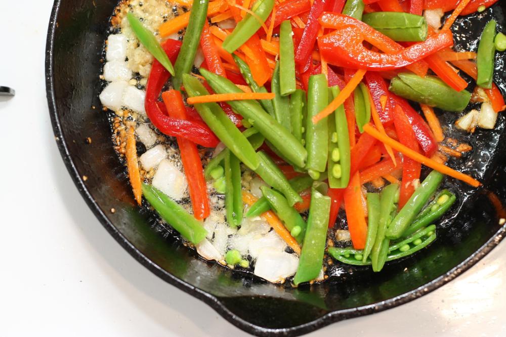 鮮やかな色合いの野菜がスキレットで調理されている