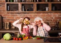 祖母と孫がキッチンで輪切りのパプリカを目に当てて眼鏡の様にしている