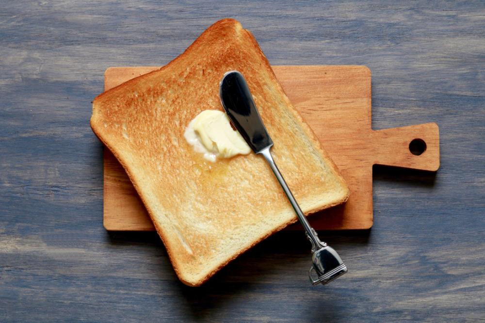 食パンにバターナイフでマーガリンが塗られている