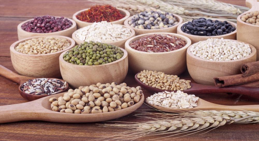 様々な種類の豆が木製の皿に盛られ、並んでいる