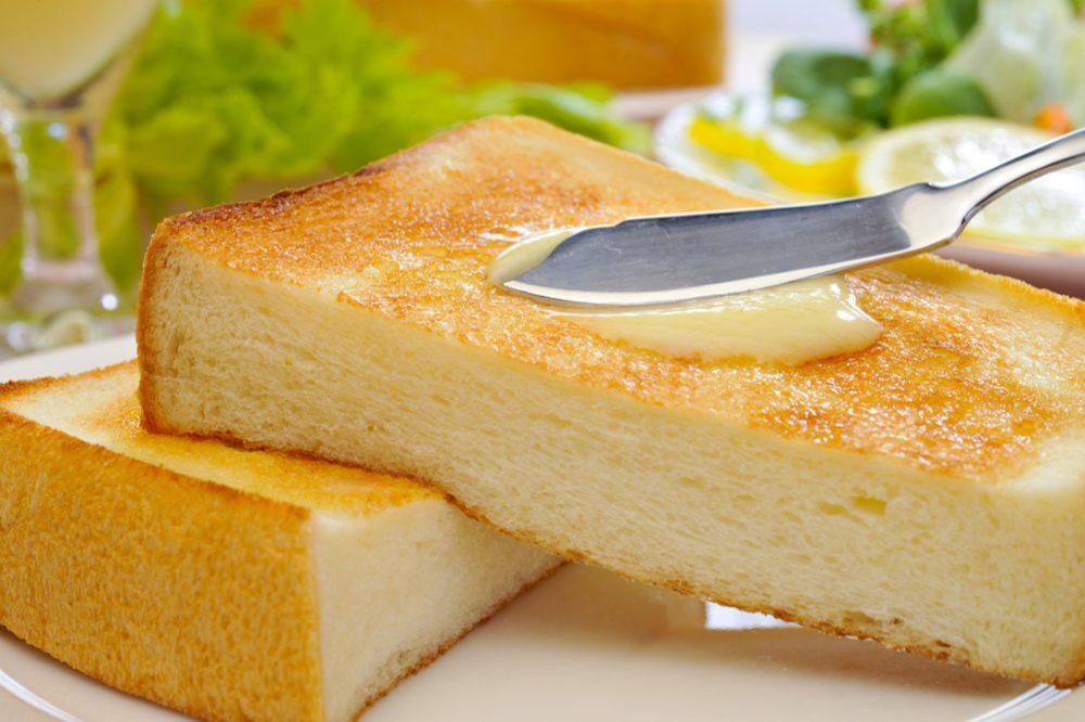 食パンにマーガリンをナイフで塗っている