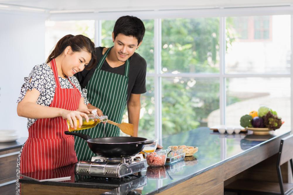 男性と女性が油を使ってキッチンで調理をしている
