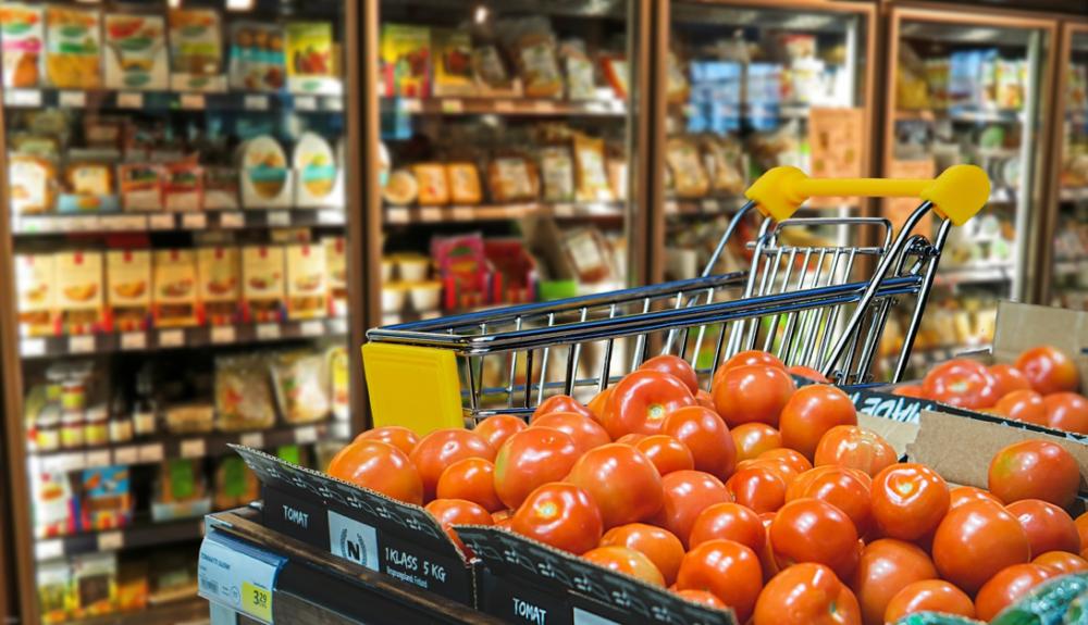 トマトが大量にあるスーパーの売り場とショッピングカート